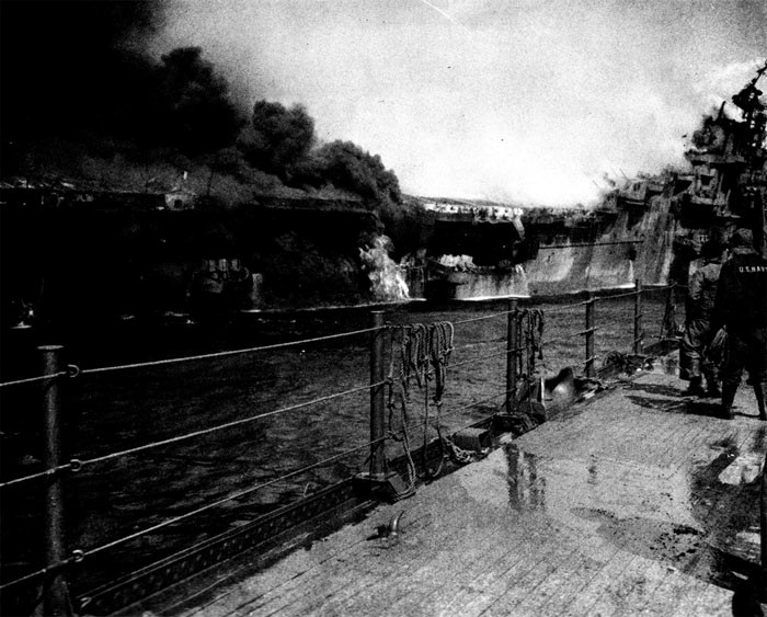 Photo 16: 19 March Action. Distant shot of fire in after part of Franklin. Burning gasoline is still pouring out of roller door opening about frame 170. Note men at stern escaping via net.