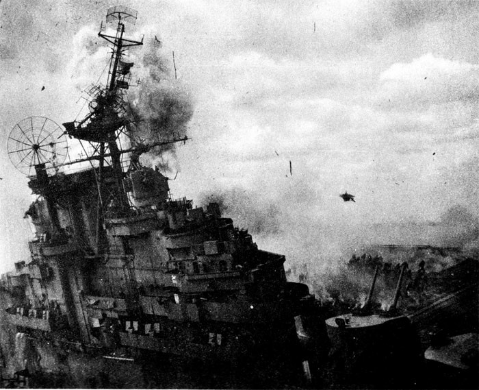 Photo 14: 19 March Action. Picture taken at the instant of a high order detonation on port side. Note debris in air and firefighters running to escape. Note topmast broken at radar platform level.
