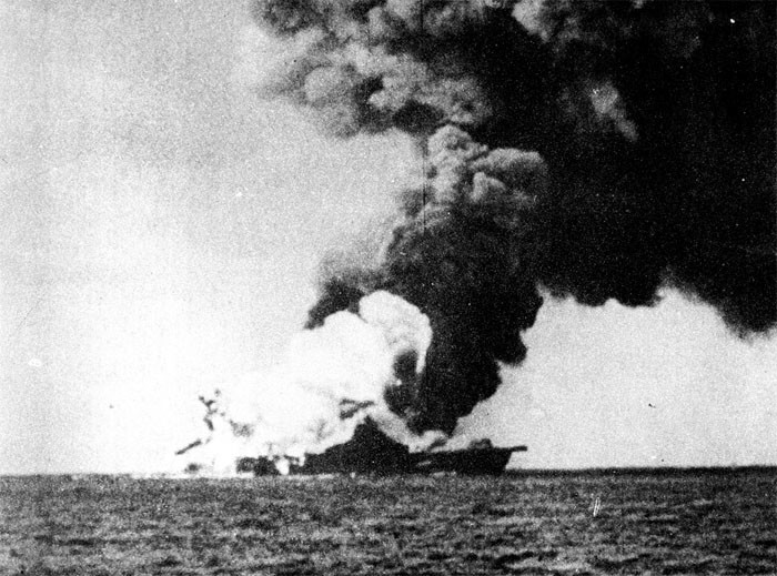 Photo 13: 19 March Action. A tremendous explosion. Note extent of high order detonation white smoke. Rockets and other pyrotechnics are distinctly visible at stern.