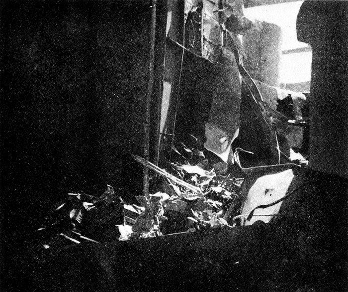 Photo 30: 19 March Action. Looking to port and up from hangar to the platform for Nos. 6 and 8 5-inch guns on port quarter. Large hole blown in gallery deck space by bomb.