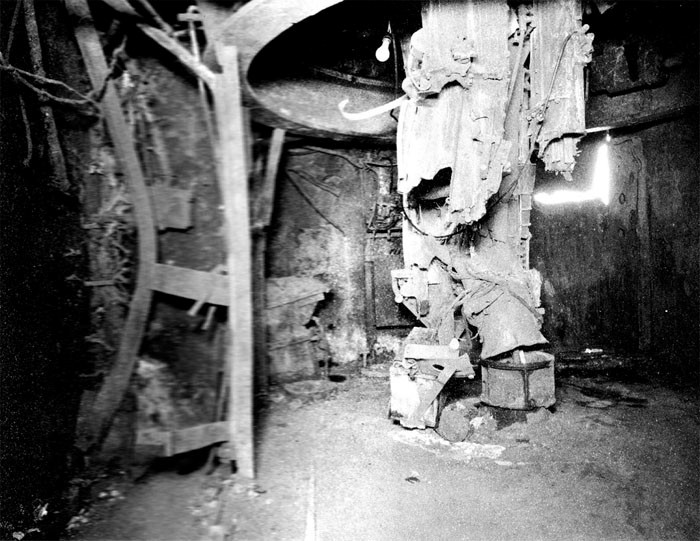 Photo 40. 19 March Action. Upper handling room No. 7 5-inch twin mount. Looking outboard to starboard. Hoists and center column destroyed by explosions and fire. Note hole in 3/4-inch STS outboard bulkhead.