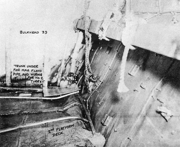 Photo No. 9: A-512-M, looking aft. The broken flooding piping is under the deck between frames 38 and 39. Note bulge in deck and crushed structure in corner. Flooding came up through deck here.