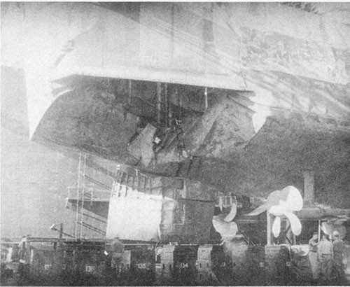 Photo No. 17: View of torpedo damage to starboard section of stern in drydock ABSD-2 at Manus. Note damage to rudder. Temporary above-water repairs were installed at Ulithi.