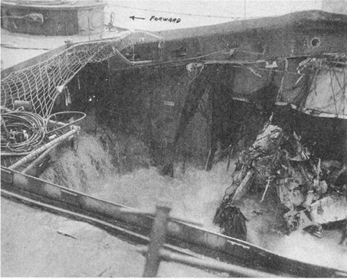Photo No. 19: View of damage to the hangar space while en route to Ulithi. Note the upward distortion of the starboard side of the main deck.