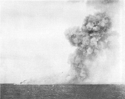 Smoke from detonation of bombs stowed in torpedo stowage. BIRMINGHAM visible at left edge of smoke.