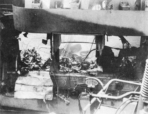 View of damage to hangar deck seen through blown-out side of hangar. Note crumpled area of hangar deck centered at about frame 78.
