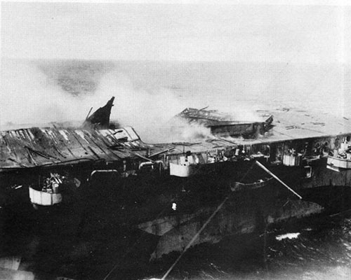 View of damage to after end of flight deck as a result of explosions in hangar. Note overturned elevator platform.