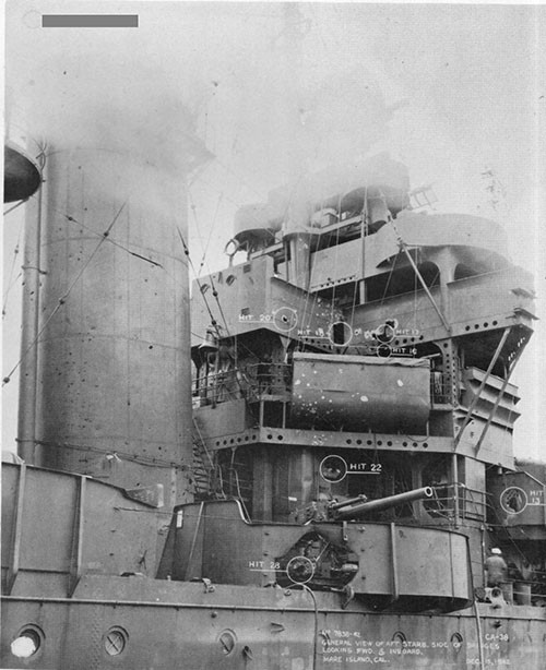 "Photo 3: Forward superstructure from starboard side. Note hit on 5"" gun No. 3 in foreground and fragment damage to the stack."