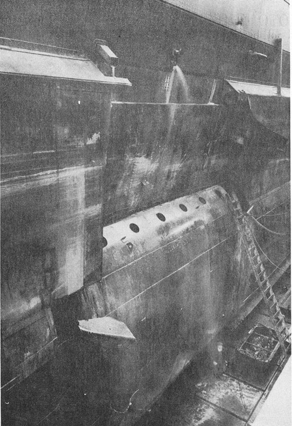 Photo 9: General view of temporary patch on arrival at Puget Sound looking aft and shoving plating peeled back action of the sea.