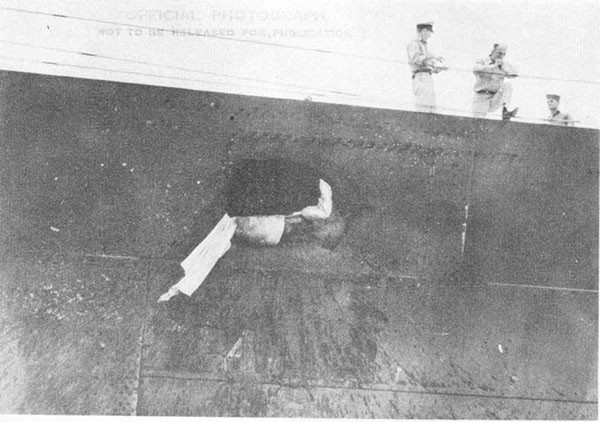 Photo 1: Hit No. 2. Hole blown in starboard sheer strake at frame 30. Note patch plates which were installed over smaller holes below sheer strake.