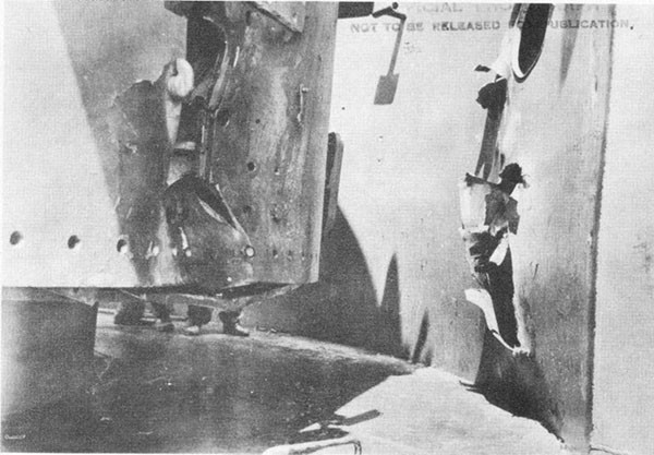 Photo 27: Hit No. 17. Port longitudinal structural bulkhead. Note damage to 5-inch mount No. 2 which stopped this projectile.