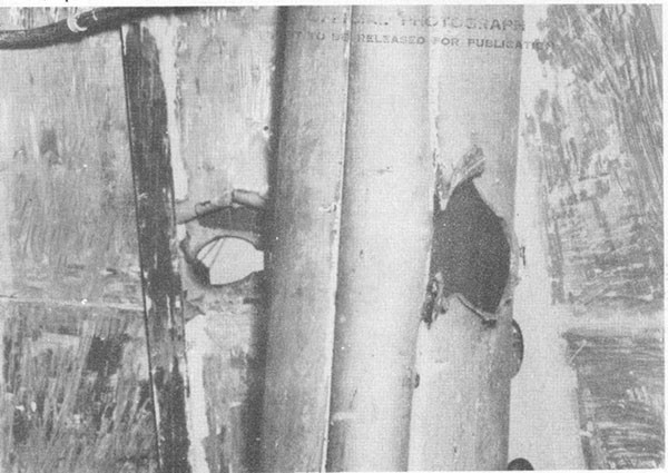 Photo 29: Hit No. 22. Hole in starboard structural bulkhead and foremast housing in battle dressing room.