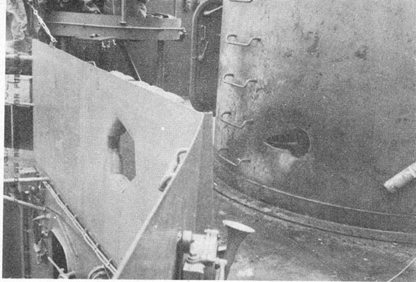 Photo 6: Hit No. 6. Projectile holes through starboard splinter shield and into 5-inch secondary battery director foundation.