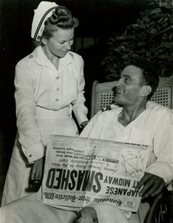 Ensign George H. Gay at Pearl Harbor Naval Hospital, with a nurse and a copy of the 'Honolulu Star-Bulletin' newspaper featuring accounts of the battle. He was the only survivor of the 4 June 1942 Torpedo Squadron Eight (VT-8) TBD torpedo plane attack on the Japanese carrier force. Gay's book 'Sole Survivor' indicates that the date of this photograph is probably 7 June 1942, following an operation to repair his injured left hand and a meeting with Admiral Chester W. Nimitz.