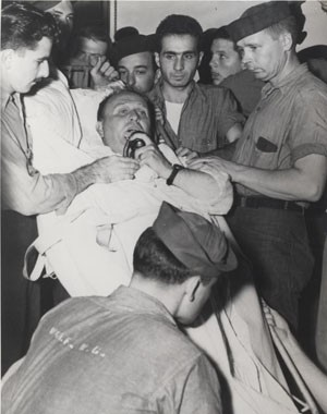 Image of Captain Dixie Kiefer, Ticonderoga's Commanding Officer, addressing the crew prior to being transferred to a hospital ship for medical treatment, in Ulithi Atoll, 25 January 1945. He had been injured when the ship was hit by a kamikaze on 21 January, while raiding Formosa. Photographic Section, Naval History and Heritage Command. Photo #: 80-G-303151.