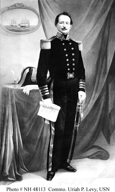 Commodore Uriah Phillips Levy, USN. Nineteenth-century albumin print of a painted portrait. It depicts Commodore Levy holding a scroll inscribed 'Author of the Abolition of Flogging in the Navy of the United States.'The uniform seen in this image features four sleeve stripes, signifying the rank of Captain. Levy died in 1862, several years prior to the adoption of this element, indicating that the portrait was painted posthumously, possibly in the 1870s or 1880s. Naval History & Heritage Command, Photographic Section, #NH-48113.