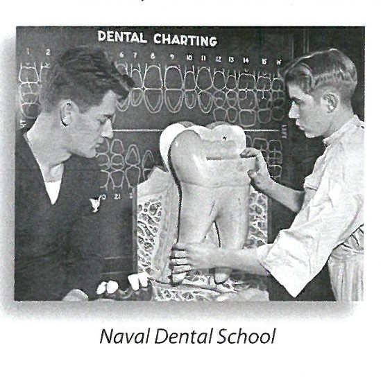 "jpeg photo titled ""Naval Dental School.""  that shows two men looking at a model of a gigantic tooth. ""Dental Charting"" is written on the chalkboard behind them."