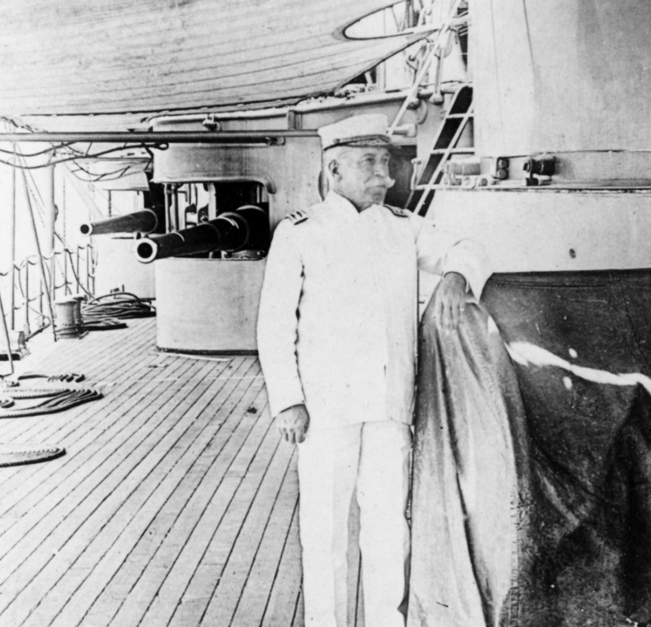 A picture of Rear Admiral George Dewey posing on the deck of the Olympia.