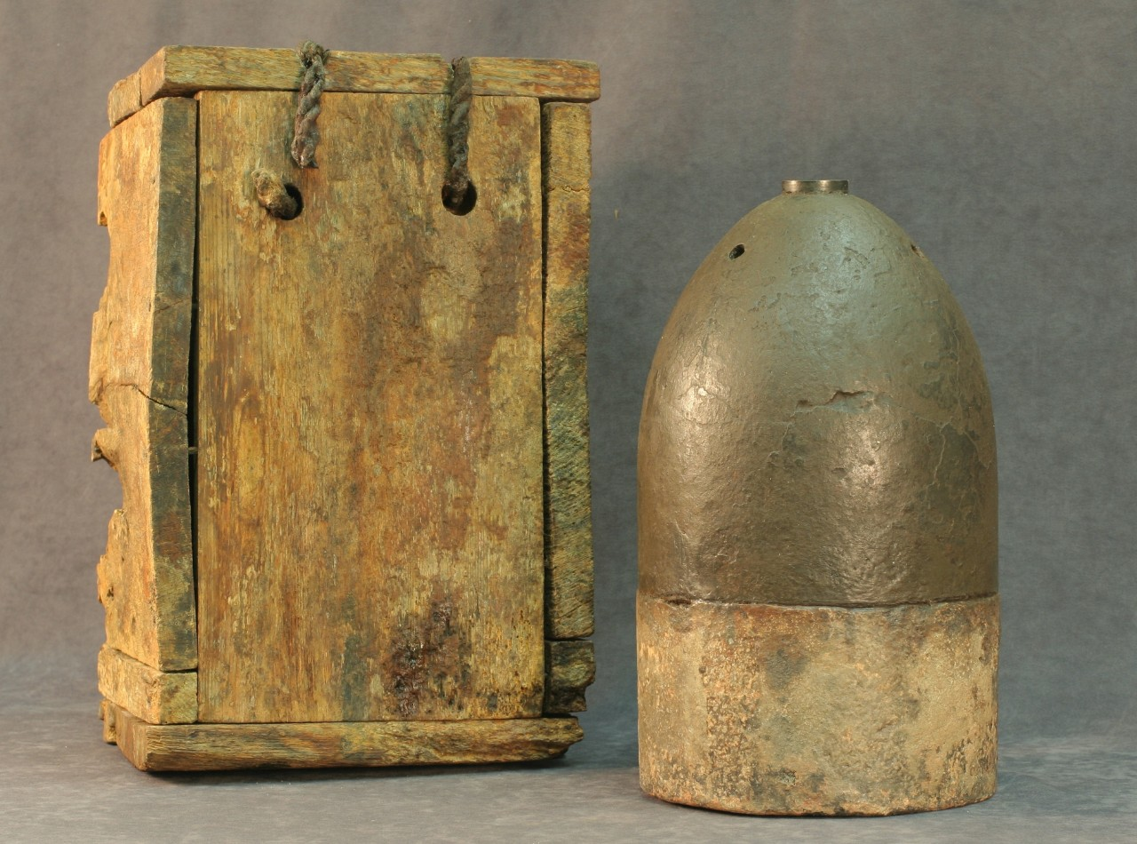A round cast iron ammunition shell called a Bitten shell resting on a round wooden disc.  A brass fuse is located on the top of the shell. On either side of the shell are two square wooden containers that when put together make a box. The Britten shell was discovered inside this box resting on the wooden disc when it was recovered.