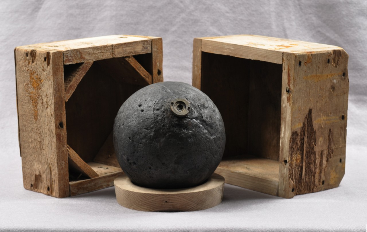 Cannon ball surrounded by its wooden storage box after conservation