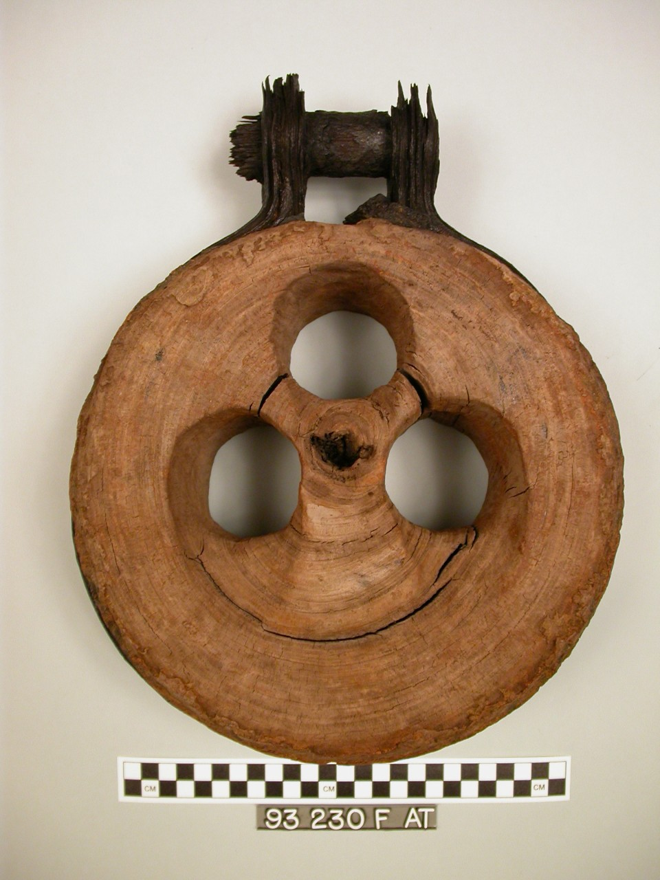 A deadeye is thick, wooden circular disc with three holes in the center one on top and two on bottom.  Encircling the wood is a piece of iron that tapers outward toward the top with an iron bolt going through it.  The iron would have attached to the ship and rope would be pulled through the holes.