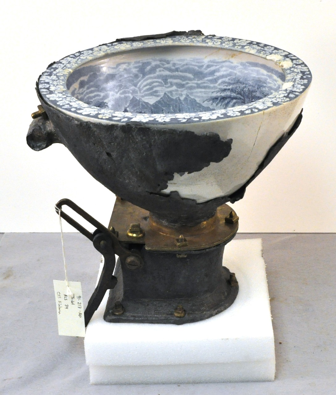 A flushing toilet recovered from CSS Alabama. A large porcelain bowl decorated with boating and country scenes set in a lead base that tapers down onto a large square brass washer.  A circular hole is made at the bottom of the bowl where a round brass door swings open and shut. Connected to the brass washer is brass handle which would allow you to operate the brass door.  The brass washer is screwed into another square lead piece below it and abruptly tapers to a circular lead piece.