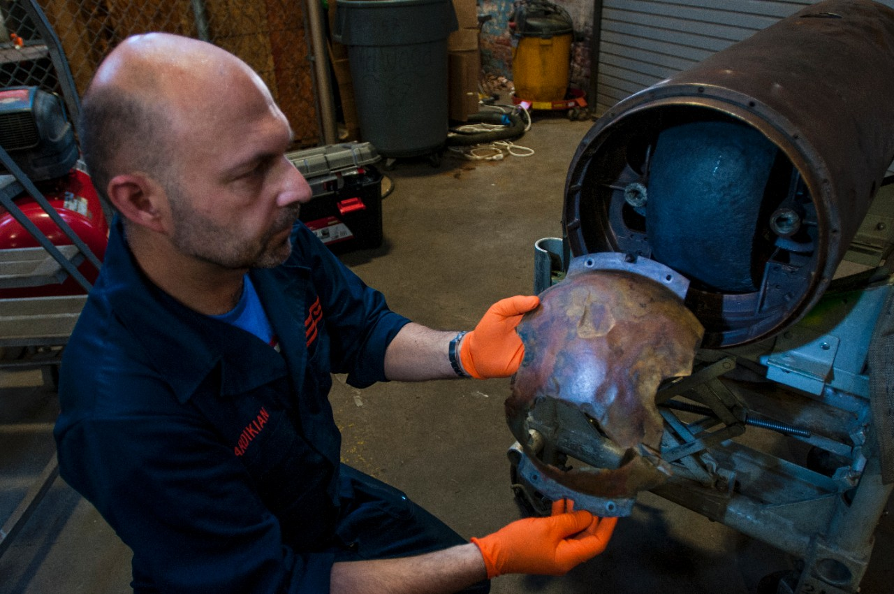 Conservator Paul Mardikian holds the oil shield in its original position over the fly wheel in the midsection of the torpedo.
