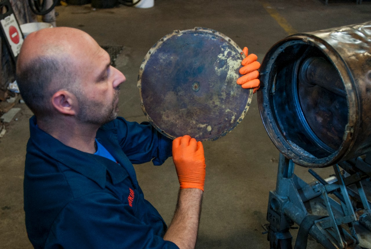 Paul Mardikian, a conservator with TerraMare Conservation and SEARCH, shows how the forward end of the middle-body section would have been sealed on the conserved Howell Mark I Torpedo No. 24