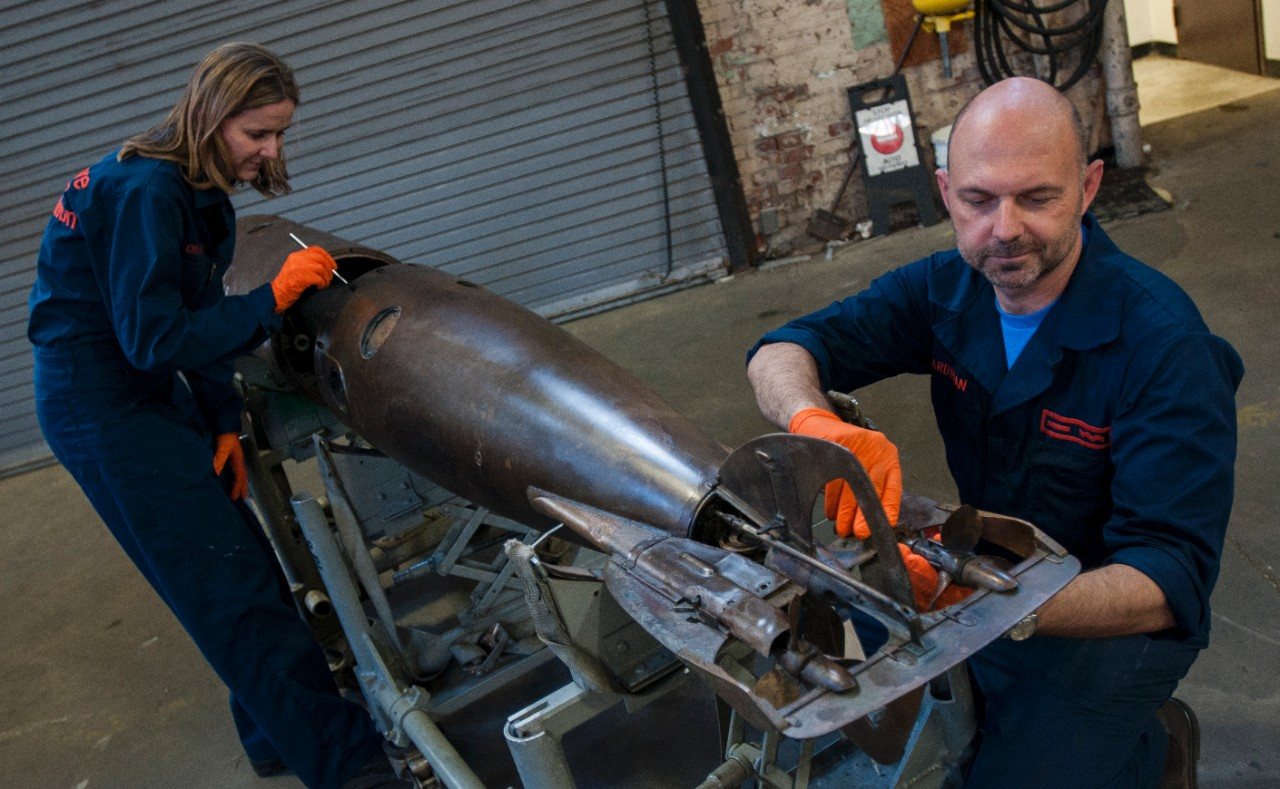 Conservators, Claudia Chemello and Paul Mardikian, perform final adjustments on the conserved torpedo to make it ready for exhibit.
