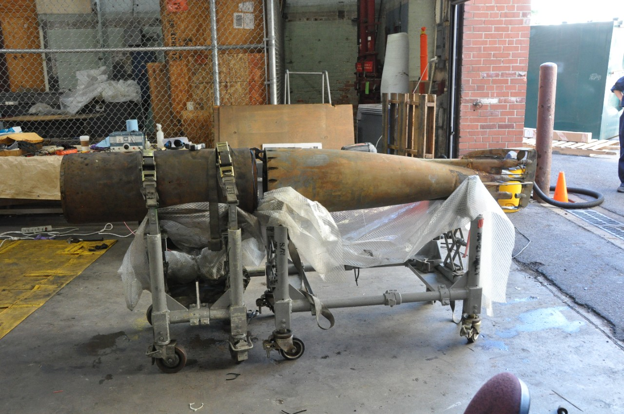 The mid and tail-sections of Howell torpedo No.24 midway through conservation placed end to end on a torpedo cart in the NHHC warehouse.