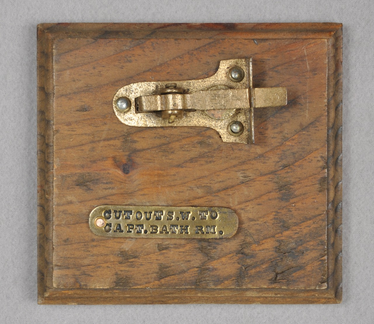 "Attached to a square wooden piece of wood is a brass cabinet latch and below the latch is an oblong brass tag with the woods ""Cut Out S.W. To Capt. Bath Rm."" stamped on it."