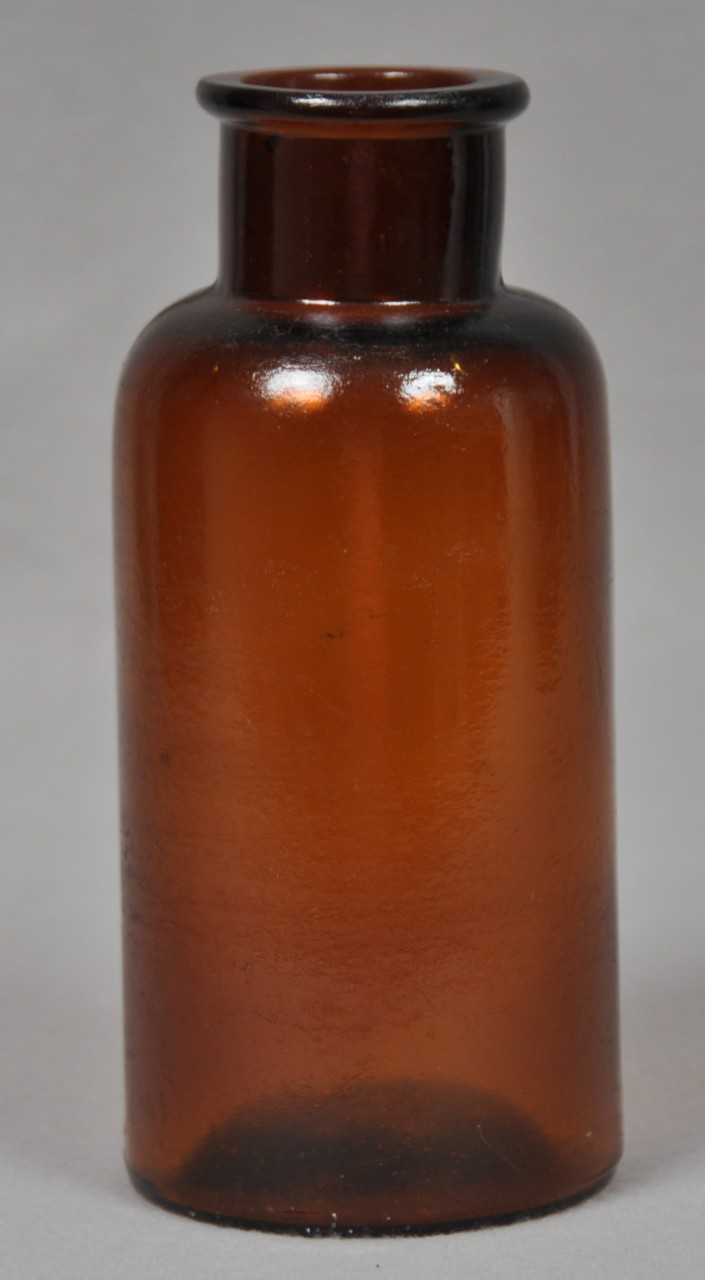 An undecorated non-screw top brown bottle.