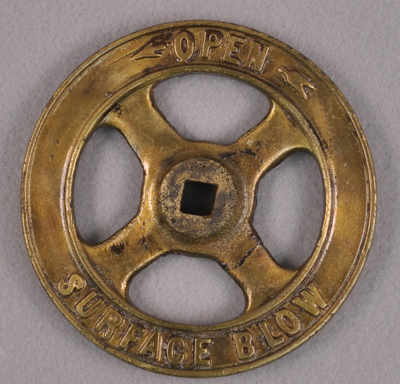 "A brass valve wheel with a raised circle in the middle. A square hole is cut in the middle of this circle.  At the top of the valve are the words ""OPEN"" with an arrow point left and the words at the bottom are the words ""SURFACE BELOW""."
