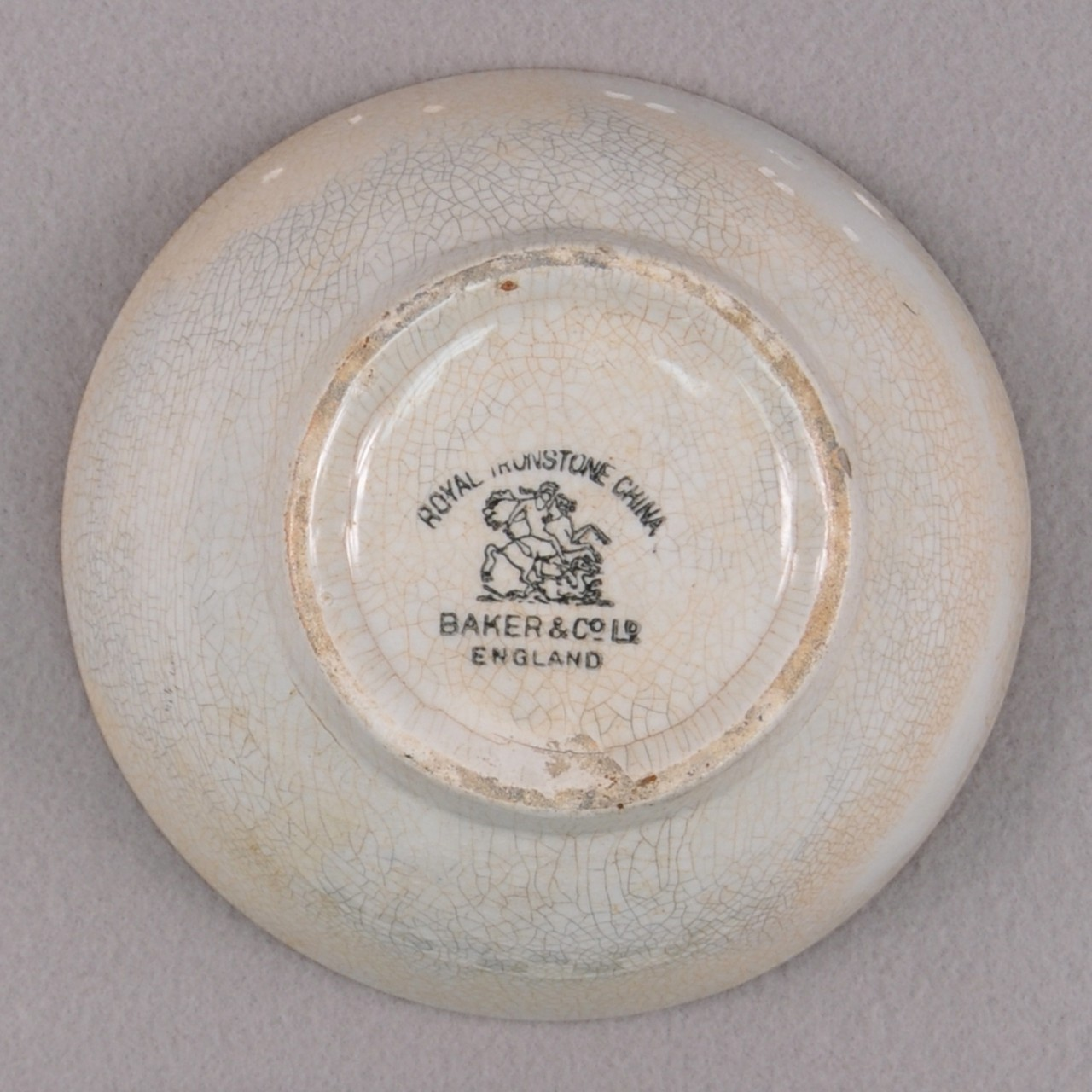 "An undecorated white stoneware bowl with cracked glaze from USS San Diego. A maker's mark of a man riding a horse and the words ""Royal Ironstone China"" and ""Baker & Co Ltd. England"" around the mark located at the bowl's base."