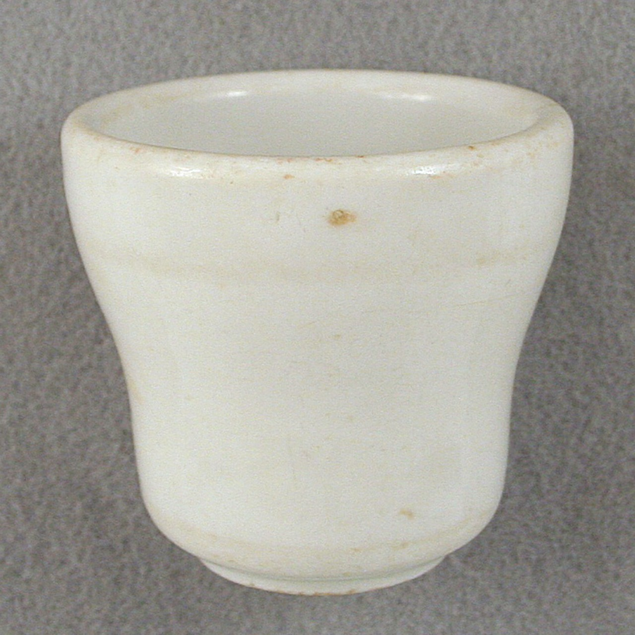 An undecorated white glazed stoneware cup from USS San Diego.