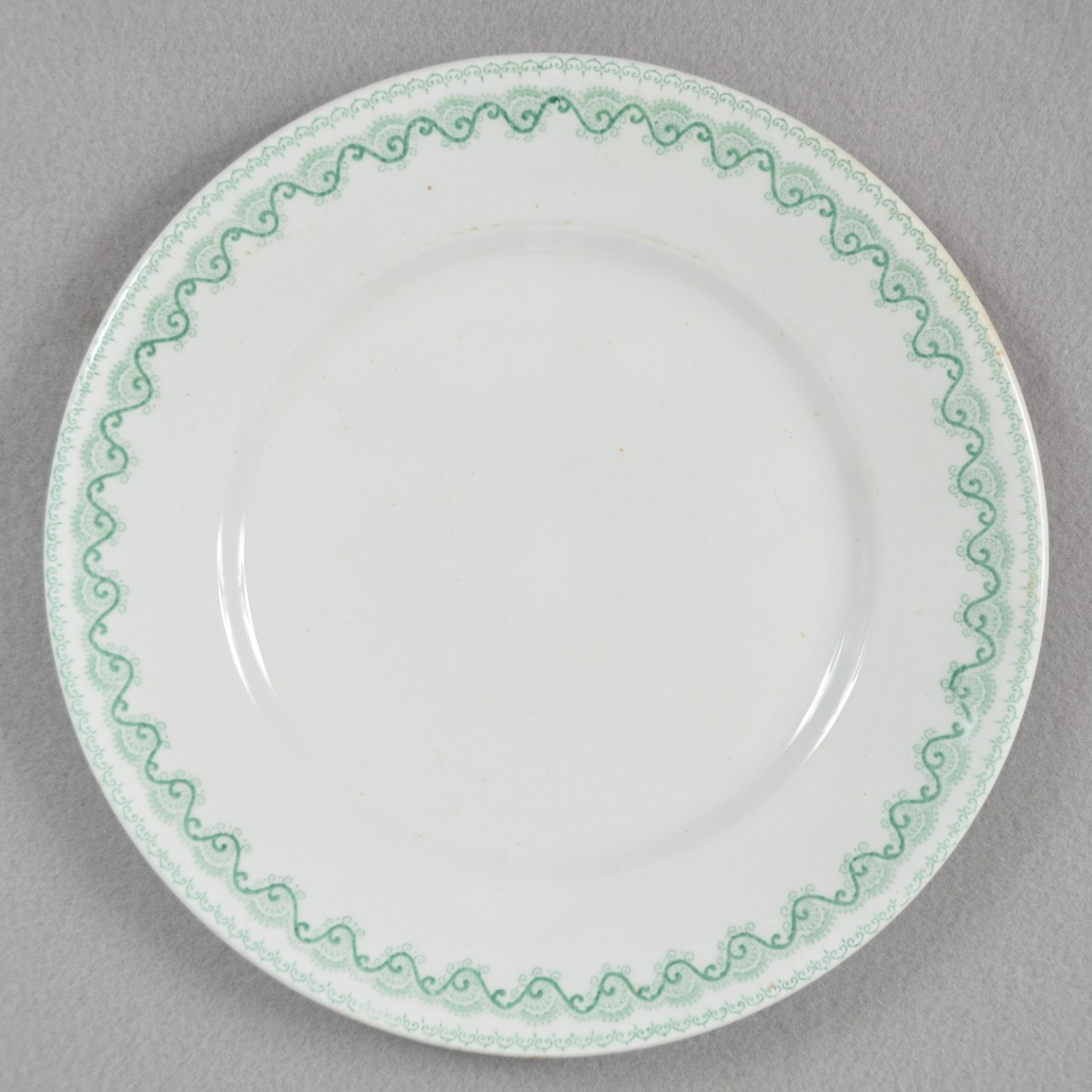 A white glazed stoneware plate recovered from USS San Diego with a continuous green scrolling pattern around the border.