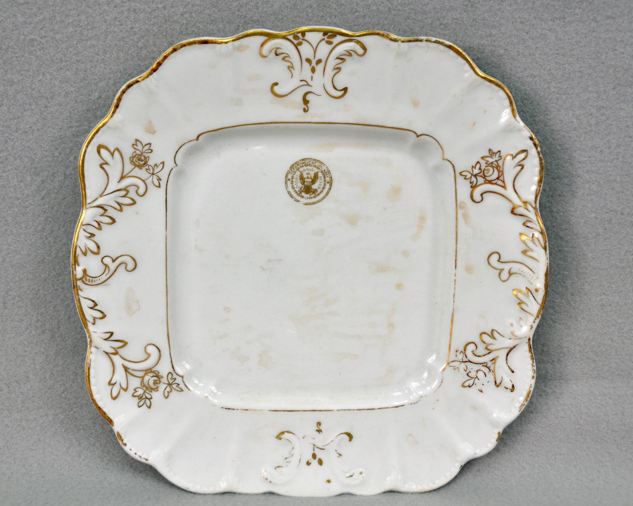 "<p>A white, ceramic, square-shaped plate. It is decorated with gilded floral molding on the lip and has a gold eagle seal that says ""Department of the Navy"" on the top.</p>"
