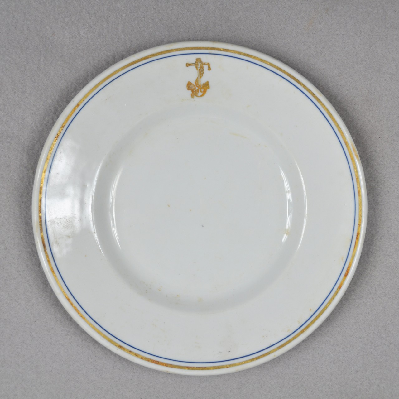 A white ceramic plate with a gold and blue ring around the edge of the face of the plate. There is also a gold anchor with a chain wrapped around it on the lip.