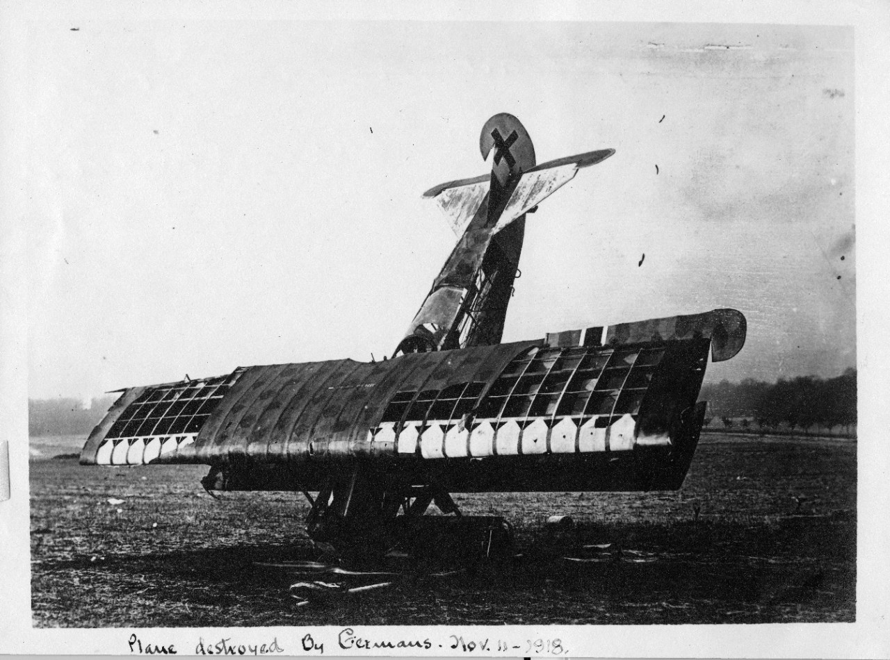 Black and white photo of a World War I plane that crashed nose first on an open field.