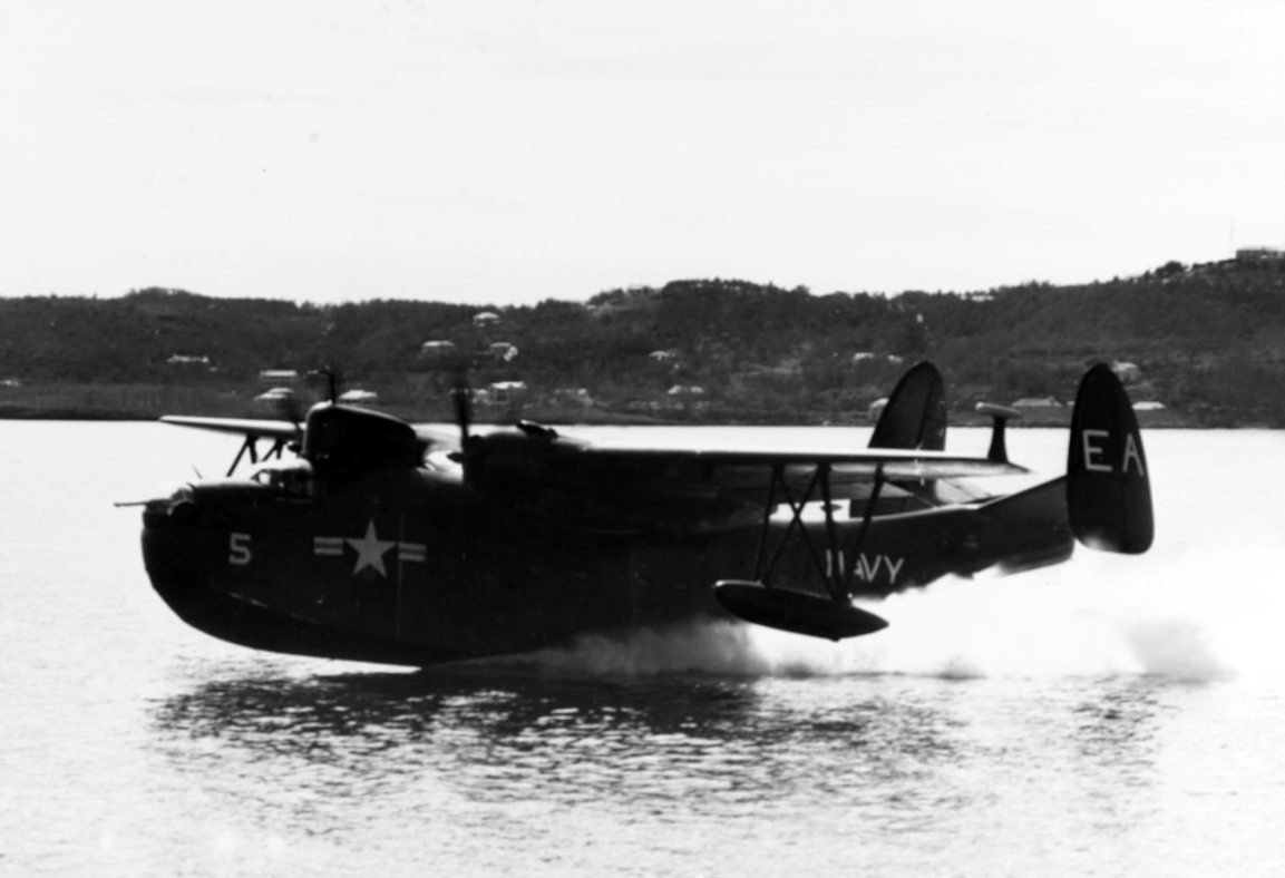 Black and white photo of a PBM-5 patrol plane just leaving the surface of the water.