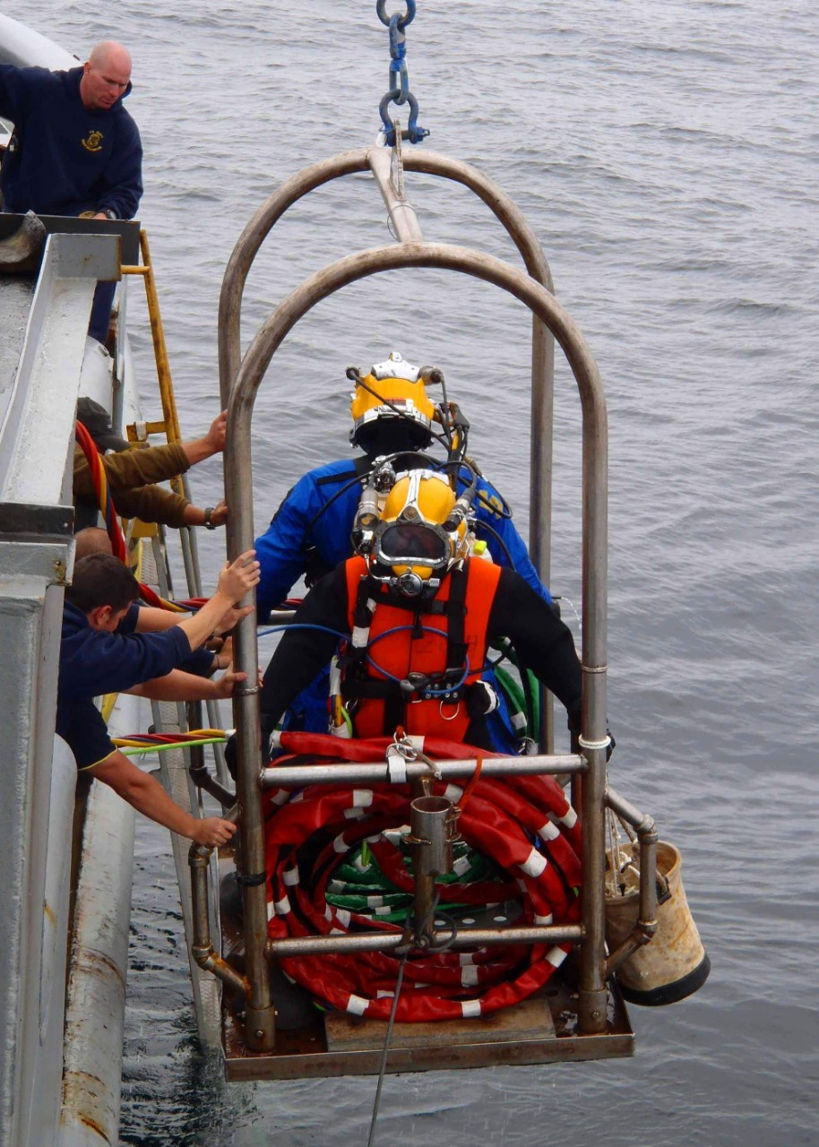 Two Navy divers wearing yellow helmets and blue dry suits on a mobile platform being lowered into the North Sea