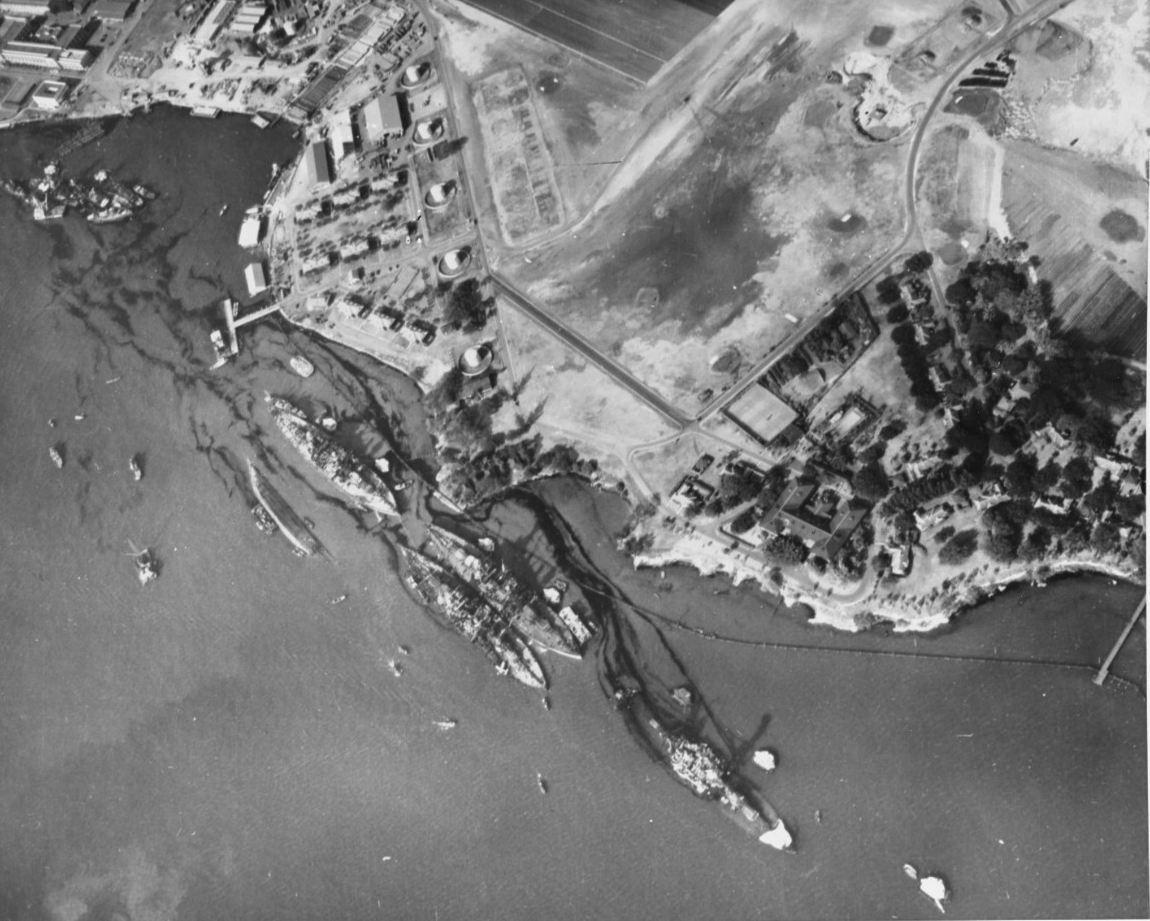 Black and white photograph looking down on the land and water of Pearl Harbor, with at six large damaged hulls leaking trails of oil.