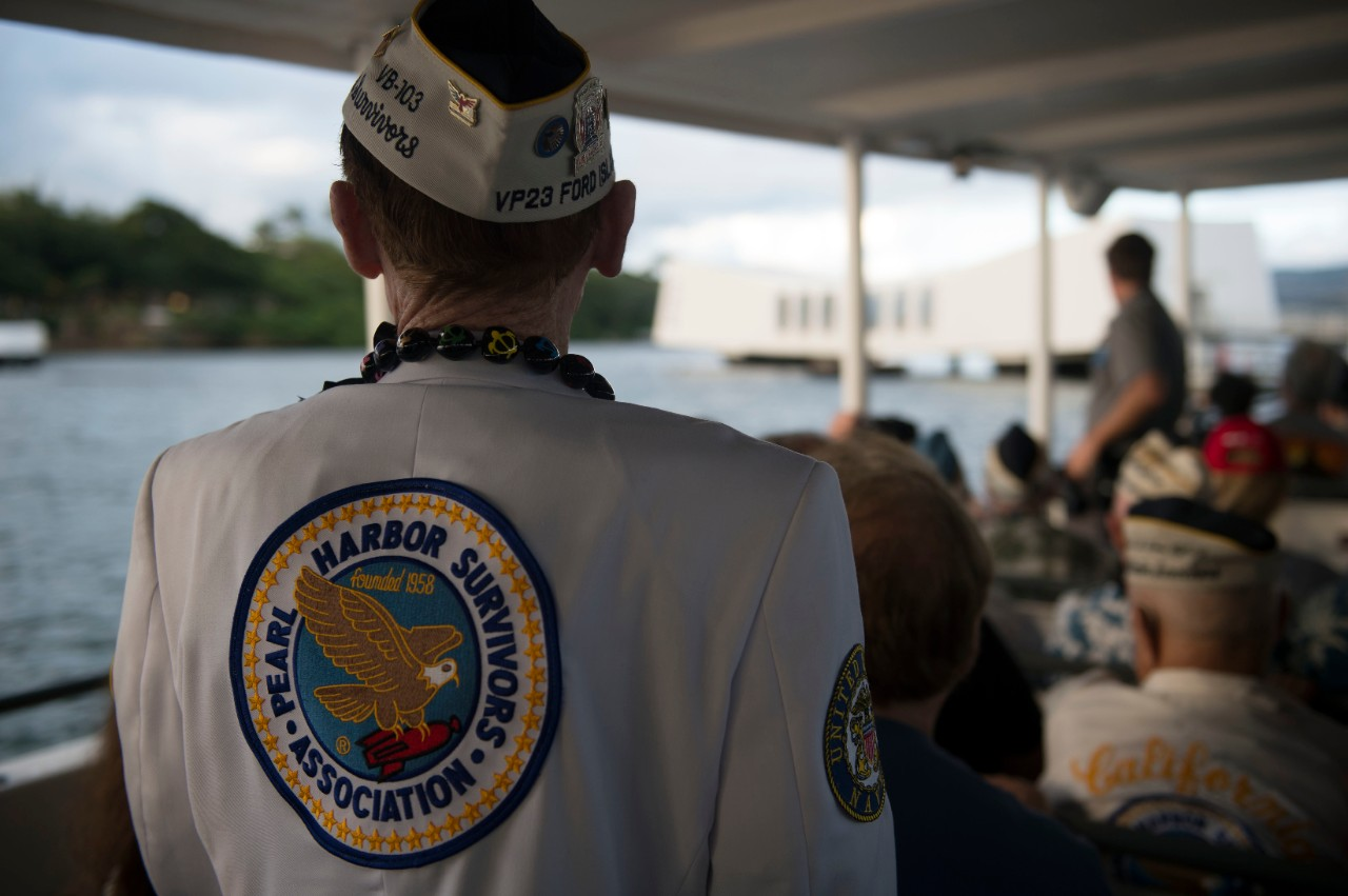 Color photo of a the back of a man wearing a jack with large patch that reads Pearl Harbor Survivors Association. The Arizona Memorial is in the background.