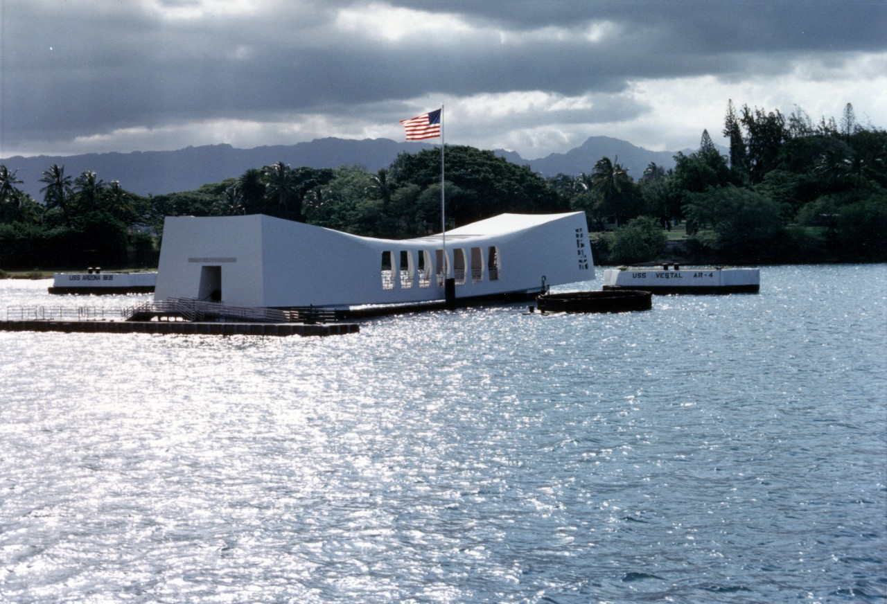 Color photo of the sun shining on the Arizona Memorial and the water surrounding it.