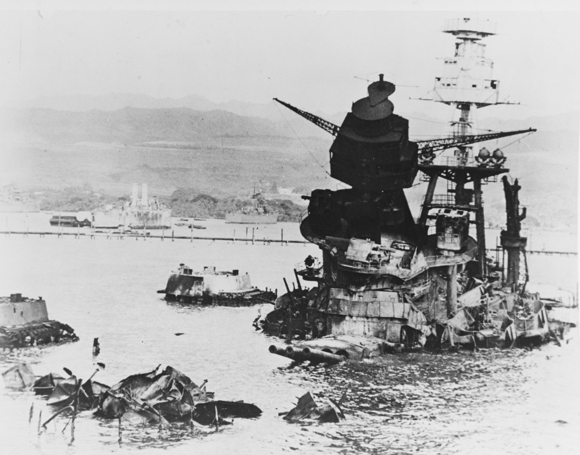 Black and white photo showing the superstructure of USS Arizona emerging from the water. The foremast is canted forward and the barrels of the three 14 inch guns of Turret 2 are elevated just above the water.