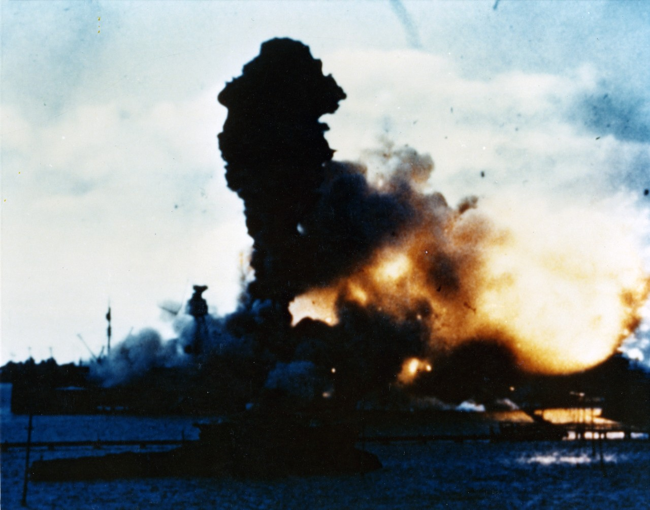 Color Photo of an explosion engulfing battleship USS Arizona (BB-39) with debris flying in the air.
