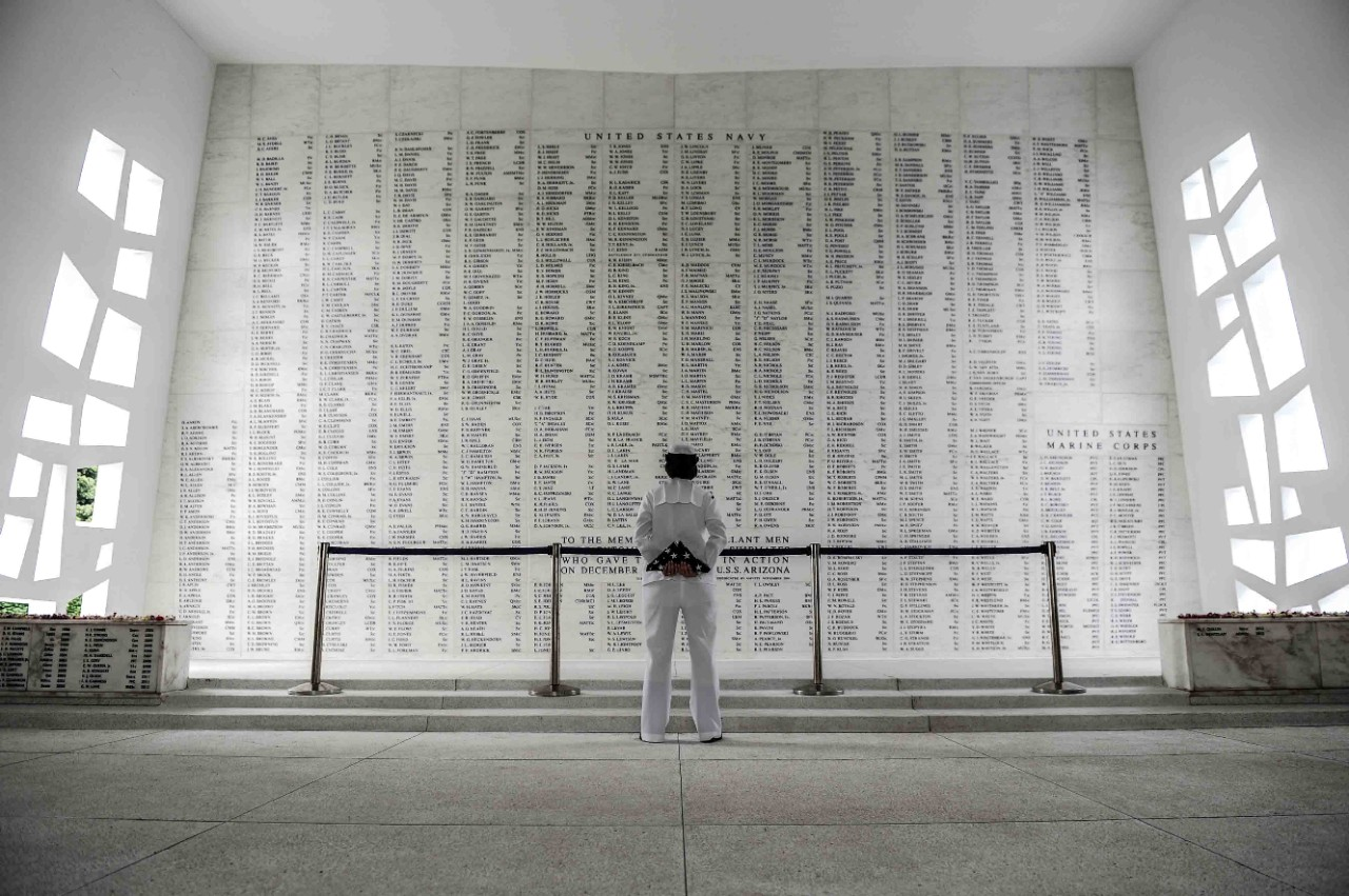 Color photo from behind a Navy Sailor in enlisted service dress white uniform centered in front of a large stone wall with 12 full columns and 2 half columns of inscribed names.